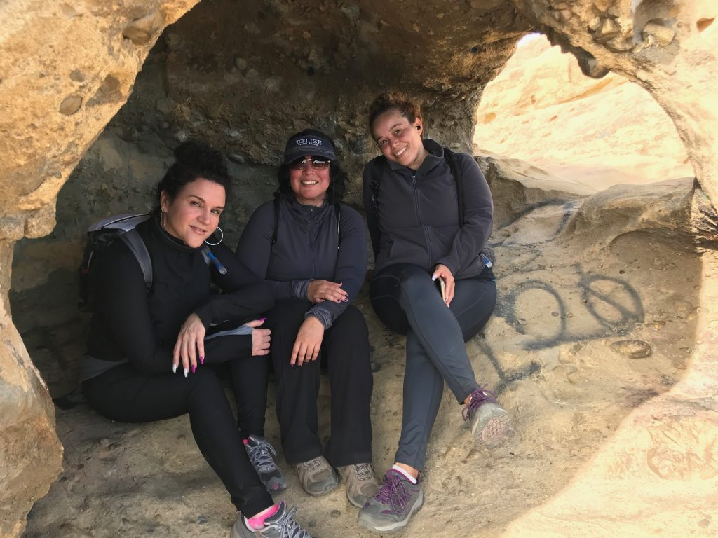 Three friends and sisters sitting inside a cave at Eagle Rock.